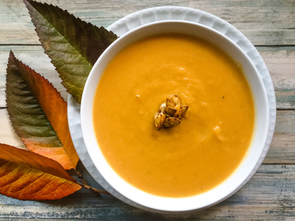 Flat lay bowl of velvetly butternut squash soup. The bowl is sitting on a plate, with a few fall leaves dangled on the table. The soup is garnished with toasted seeds from the butternut squash.