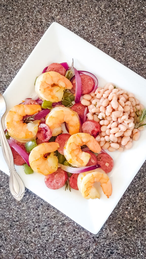 Sheet pan shrimp and sausage dinner on a plate with white beans.